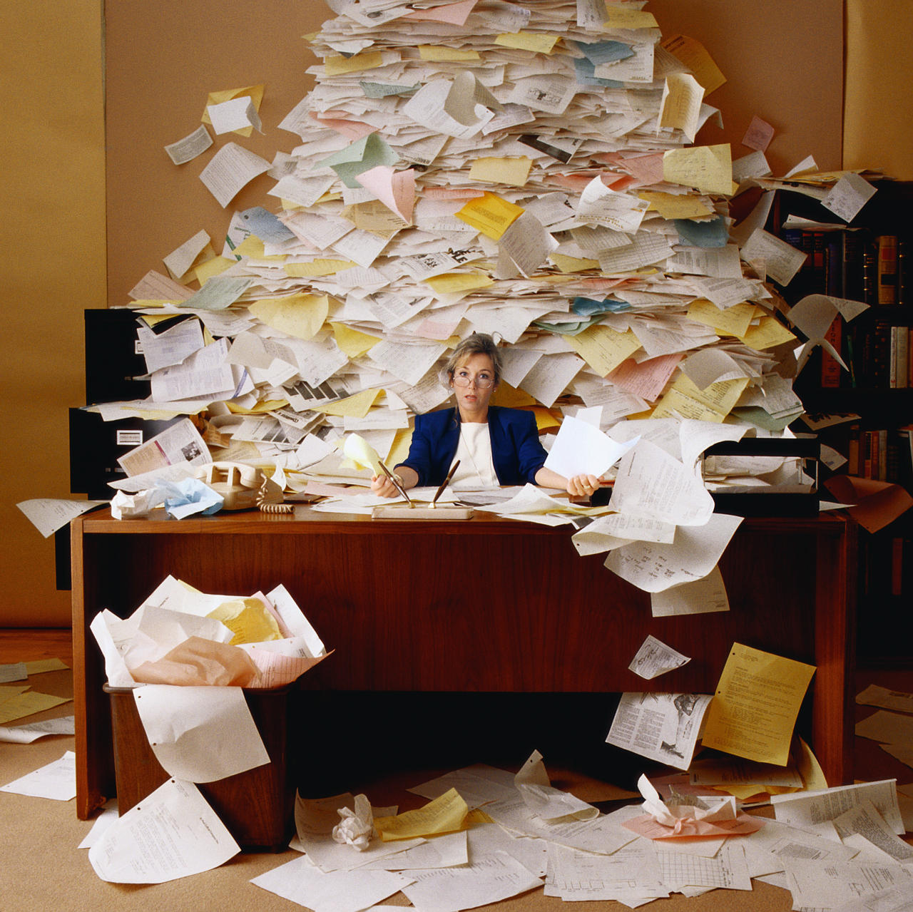 A woman surrounded by a deluge of paper work