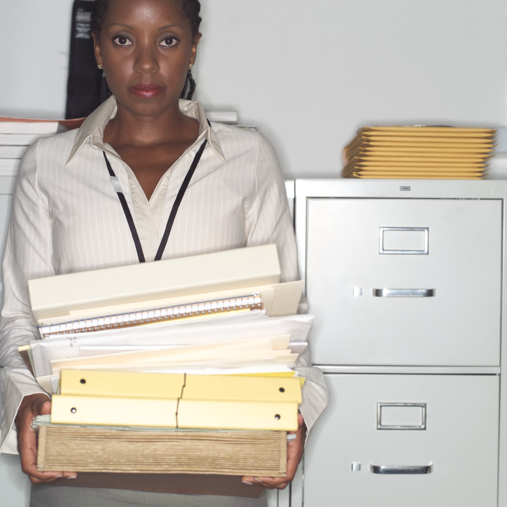 An administrative assistant stands with a neat pile of filing next to a filing cabinet.