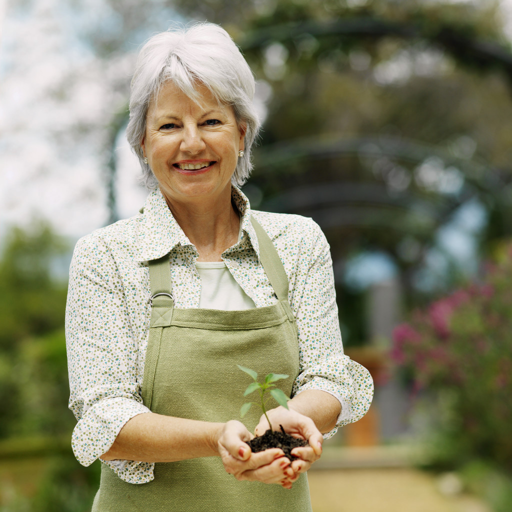A gardener wearing an apron, holds a small plant towards the person taking the picture and smiles.