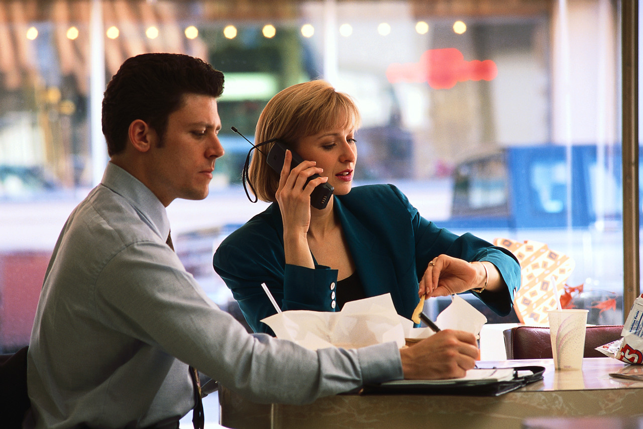 Two people in a restaurant, one is looking at her watch while on a mobile phone.